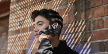 Man wearing black jacket talking on the phone while leaning against brick wall, technology, mobile, digital