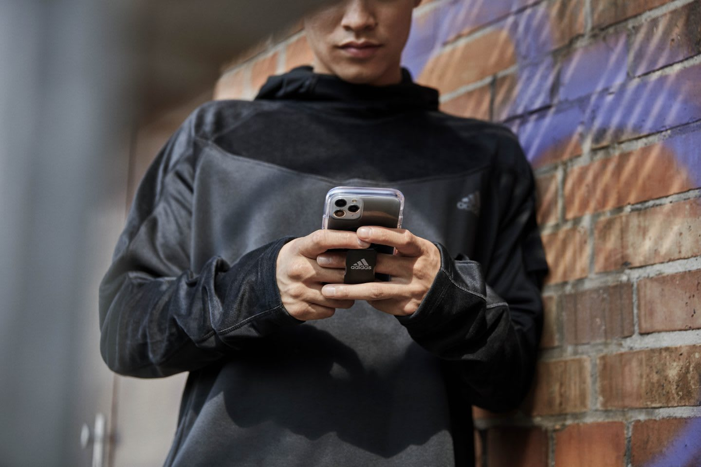 Man wearing black texting on mobile phone with black adidas case while leaning on brick wall, adidas, mobile, digital, remote, technology