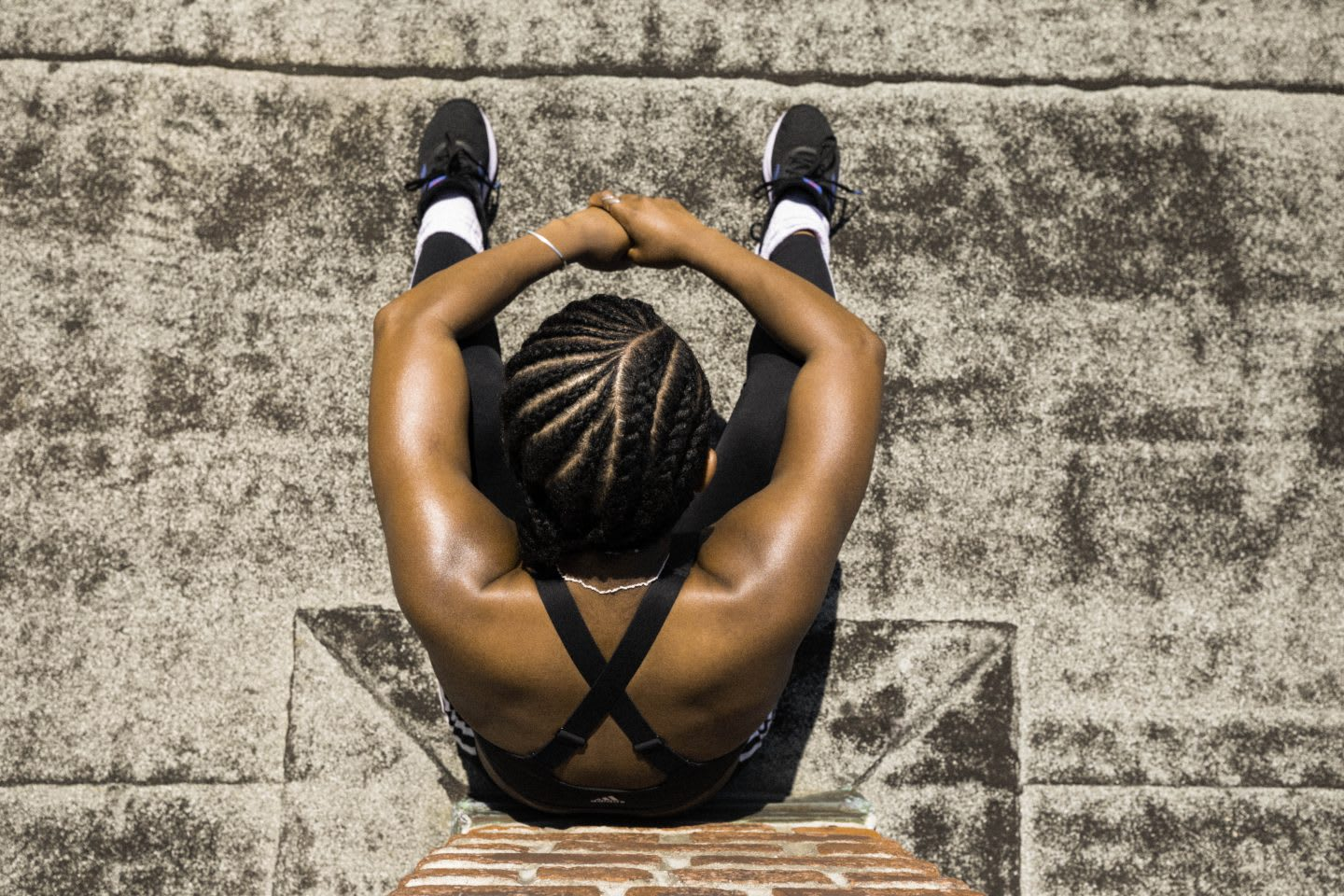 Woman wearing black sports bra, black running tights and black running shoes sitting with knees up against brick wall in the sun, athlete, rest, recovery, tired, adidas, sport, fitness
