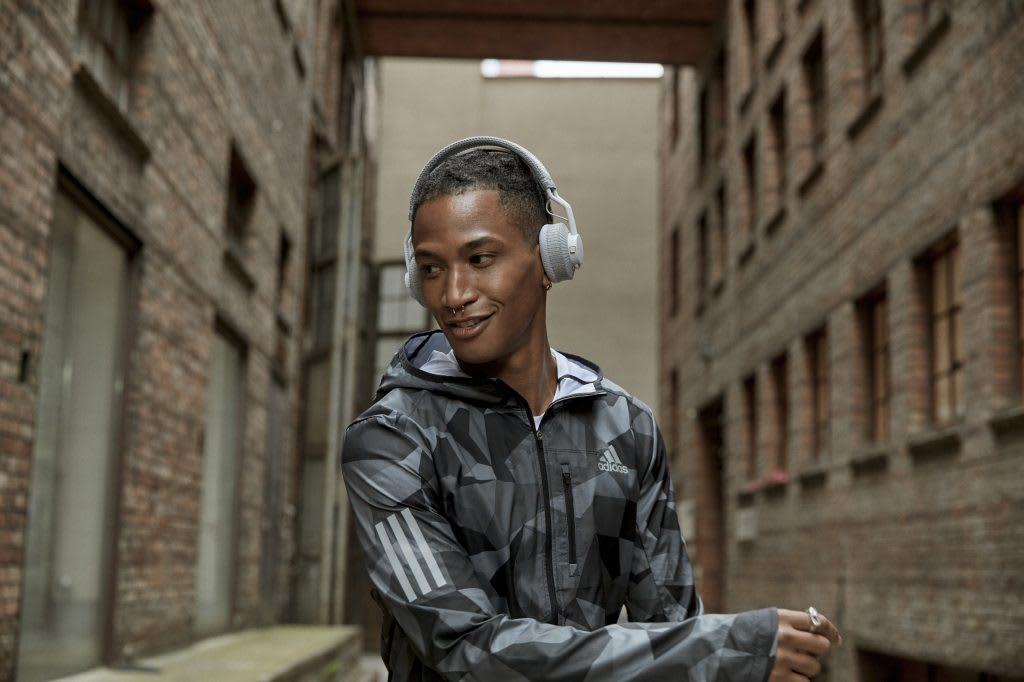 Man wearing grey and black jacket and white headphones standing on a street between buildings listening to music, running, sport, fitness, adidas