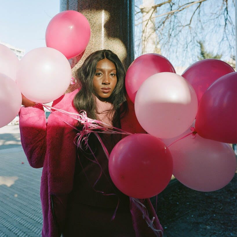 Woman holding pink and red balloons posing and staring at the camera, race, Ziwe May, inclusion, podcast