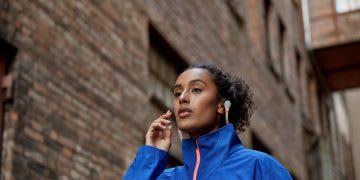 Woman wearing blue jacket wearing headphones while walking through city, adidas, sports, headphones, podcast, running, jacket, blue