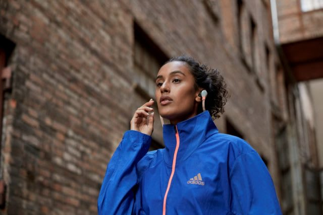 Woman wearing blue jacket wearing headphones while walking through city, adidas, sports, headphones, podcast, running, jacket, blue