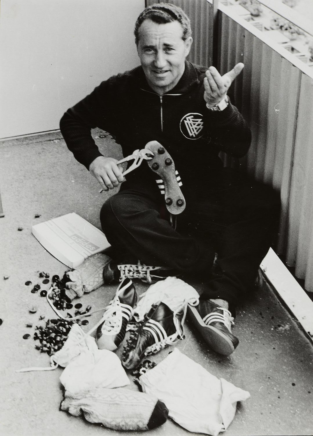 Black and white photo of man sitting on the ground using tools to build vintage football boots, Adolf, Dassler, Adi, adidas, sports, shoes, shoemaker, history, archive
