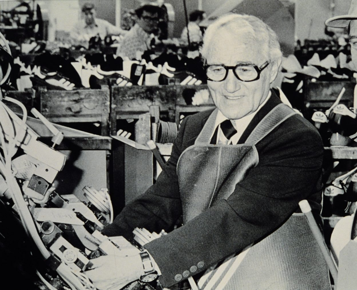 Old photo of a smiling old man wearing glasses in a shoe factory wearing apron, Adolf, Dassler, Adi, adidas, sports, shoes, shoemaker, history, archive