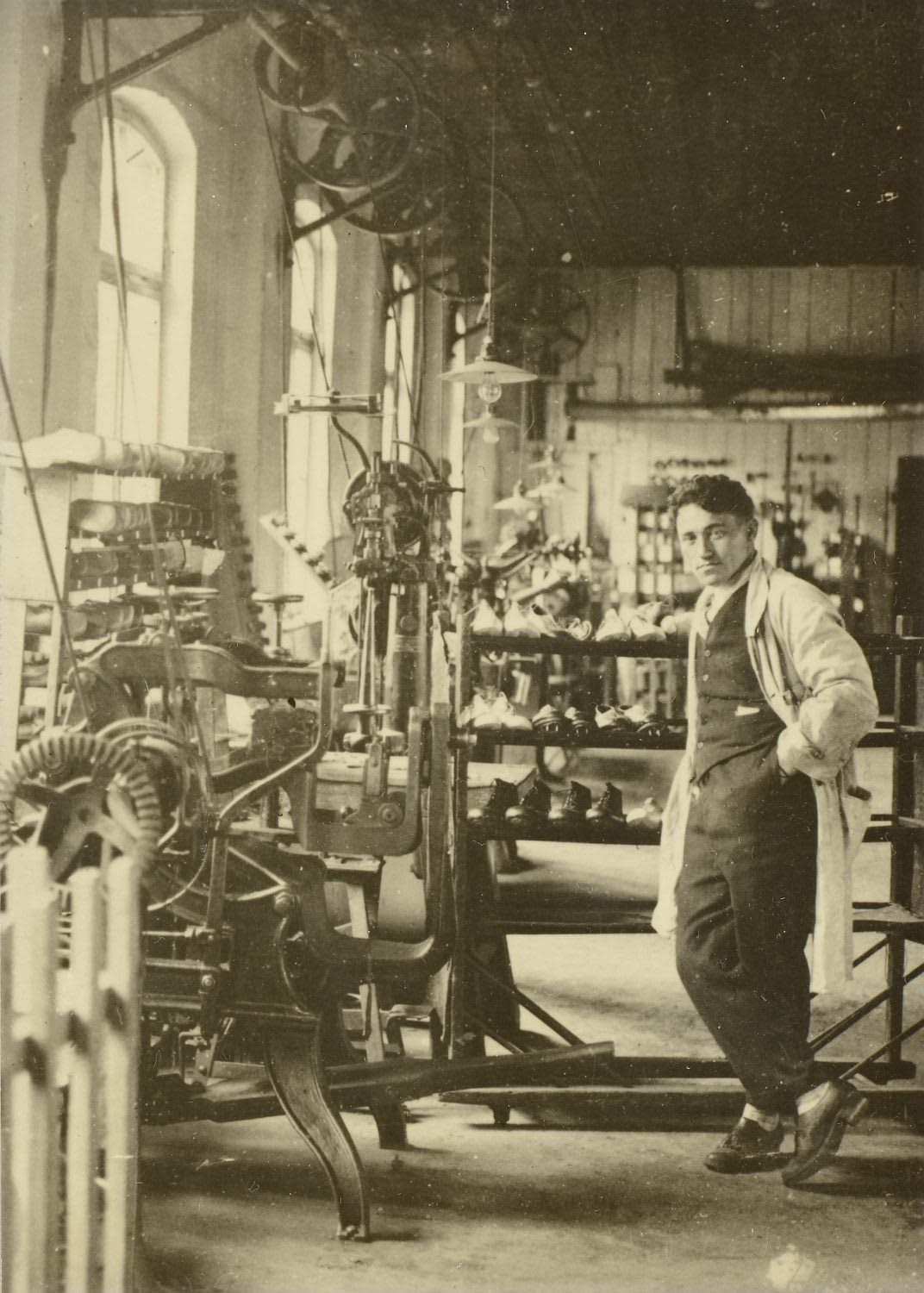 Man wearing lab coat standing next to machinery in a factory, Adolf, Dassler, Adi, adidas, sports, shoes, shoemaker, history, archive, legacy, 1930