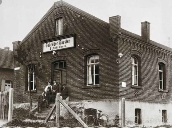 Old brick building with family standing outside, factory, black and white, Gebrüder, house, Adolf, Dassler, Adi, adidas, sports, shoes, shoemaker, history, archive, 1927, brothers, Herzogenaurach