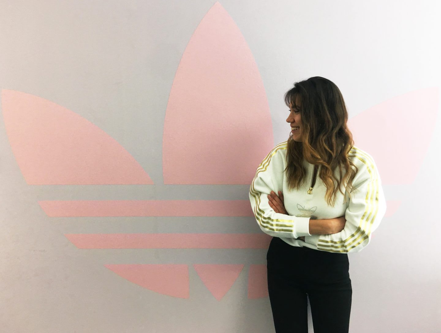 Girl with brown hair wearing cream adidas sweatshirt smiling and standing with arms crossed in front of pink adidas Originals Trefoil logo on the wall, İpek Ünlü, career, internship, adidas, virtual