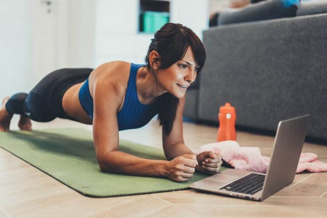 Strong sporty woman is doing working out at home and doing plank in front of her laptop, workout, exercise, home, laptop