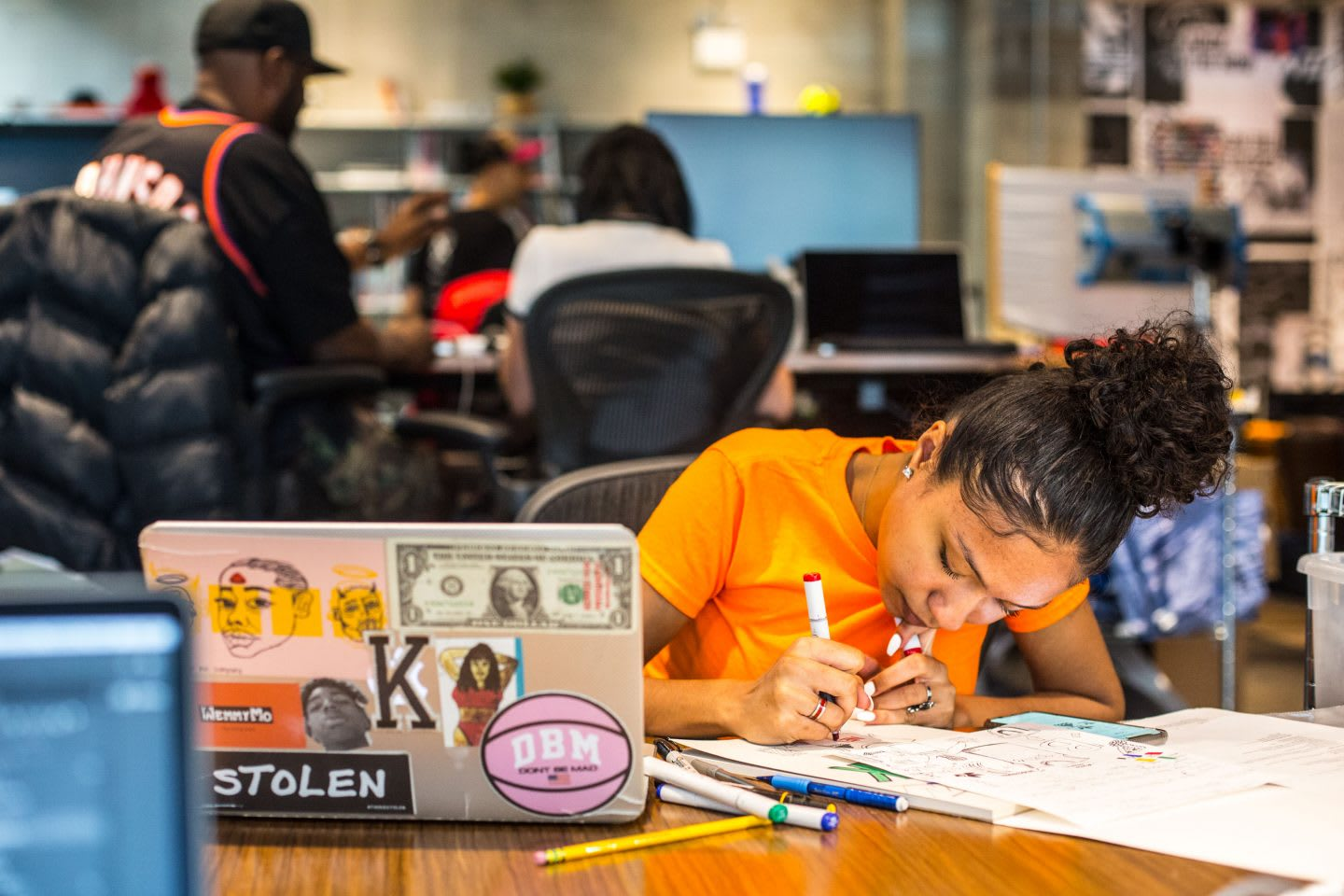 Girl wearing orange t-shirt concentrating while sketching, adidas, Brooklyn Creator Farm, Kim Aponi, designer, entrepreneur