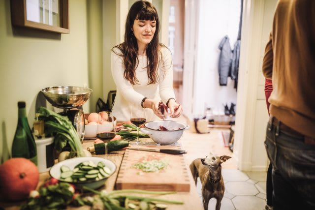 Young woman preparing meal with dog in kitchen, food, meal, dinner, vegetables