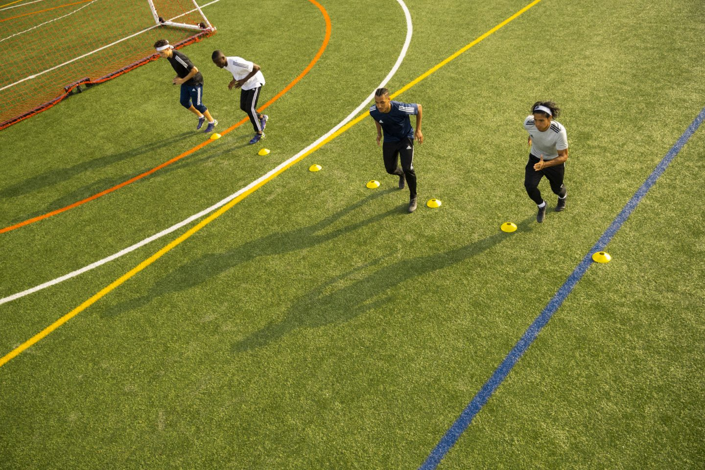 Men lining up on a football field to perform football drills, soccer, football, sports, exercise, fitness, adidas