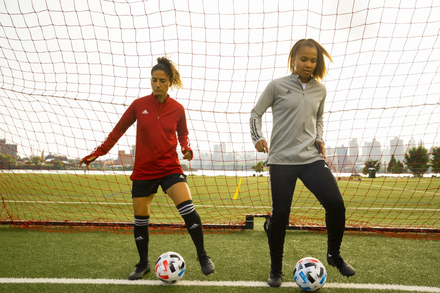 Two women dribbling footballs on a field in front of a goal, sports, football, soccer, exercise, fitness, adidas