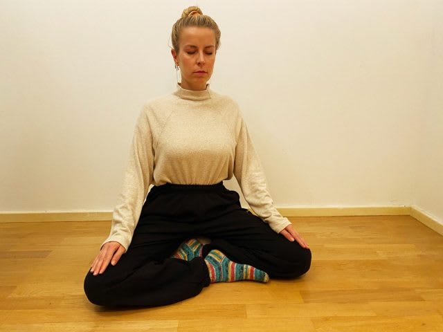 Blonde girl sitting in meditation pose with eyes closed on the floor, meditation, focus, mindfulness, Vipassana