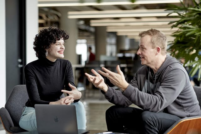 Man and woman discussing work in a conversation at the office, mentoring, adidas, employees, teamwork
