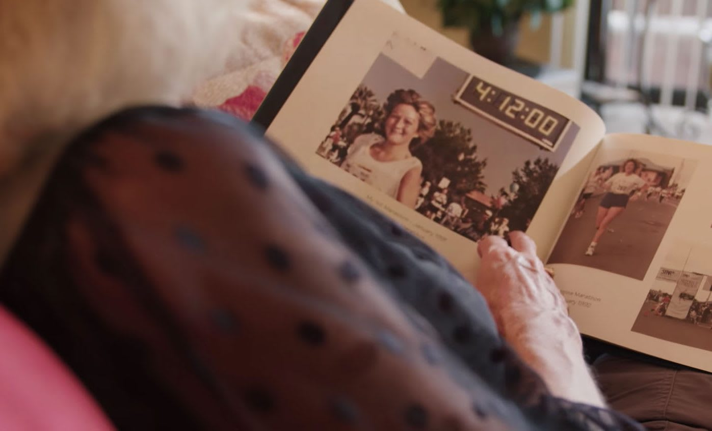 Older woman looking at old picture of herself in a scrapbook, picture, memory, EXOS