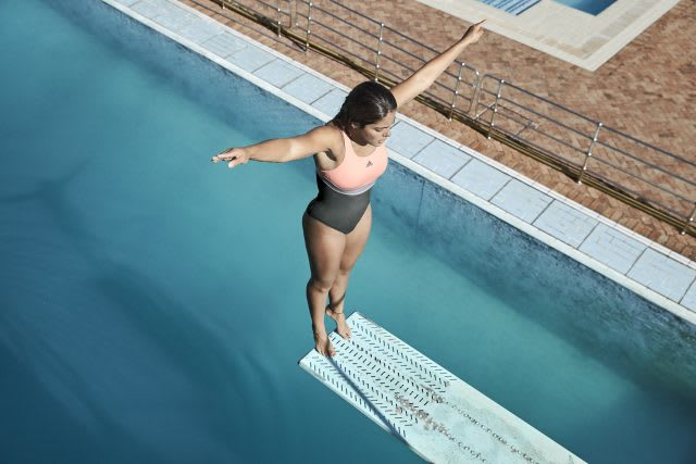 Female diving standing at the end of diving board above an outdoor pool, pool, swimming, swim, sport, fitness