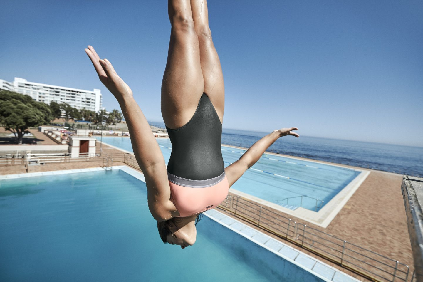 Female diver diving into an outdoor pool headfirst, pool, swimming, swim, sport, fitness