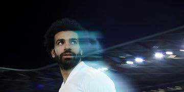 Man wearing white shirt looking behind him, Mo Salah, football, soccer, player, adidas, athlete, sport