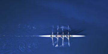 Aerial shot of rowing team rowing on water, teamwork, sports, fitness, rowing, river