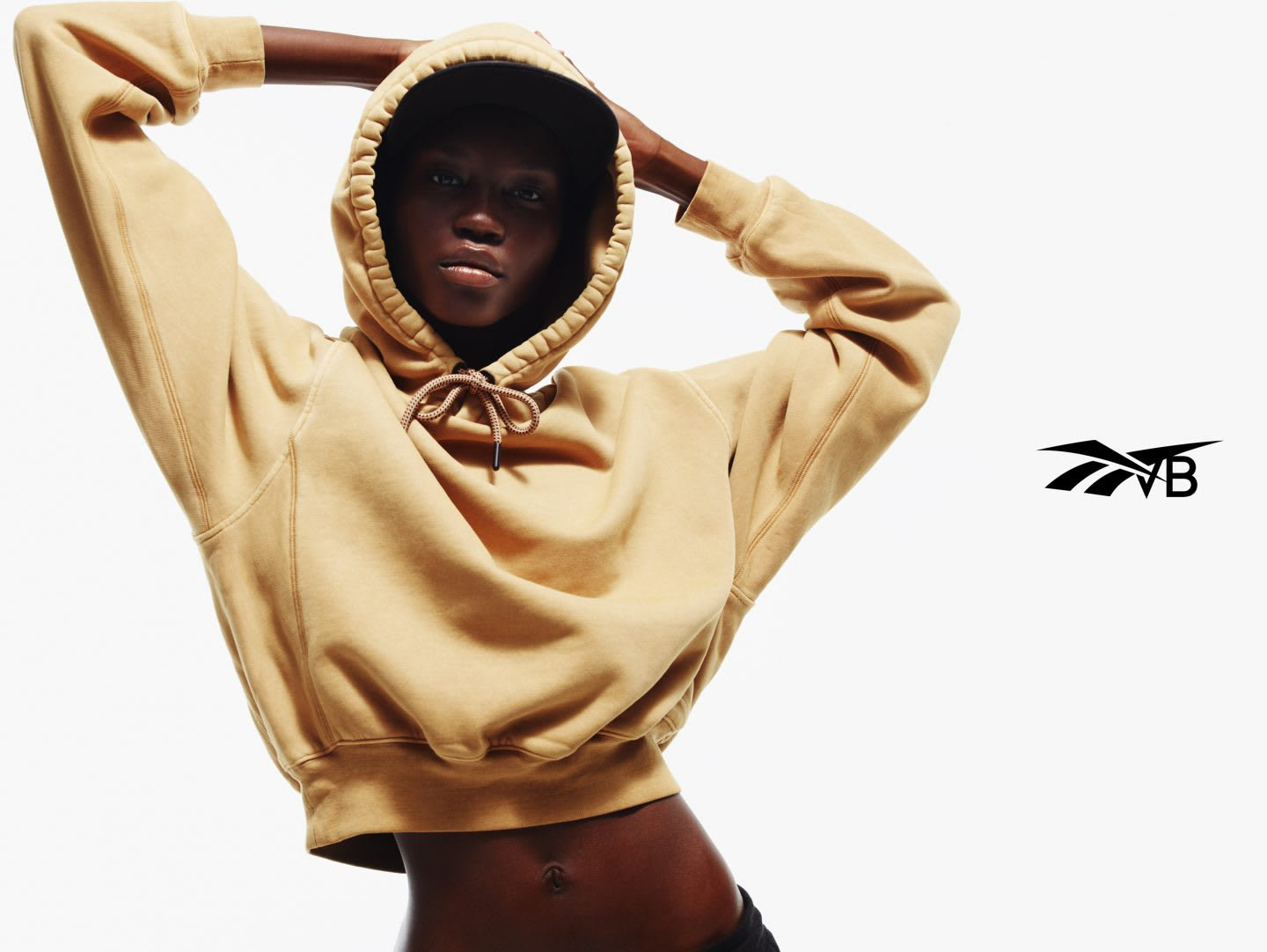 Black model wearing VB x Reebok cropped yellow hoodie from streetwear collection, Victoria Beckham, Reebok, collaboration, fashion