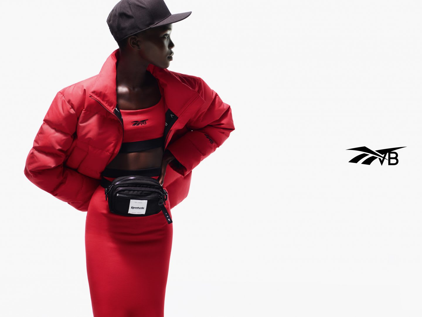 Black model wearing VB x Reebok red puffer jacket and skirt from streetwear collection, Victoria Beckham, Reebok, collaboration, fashion