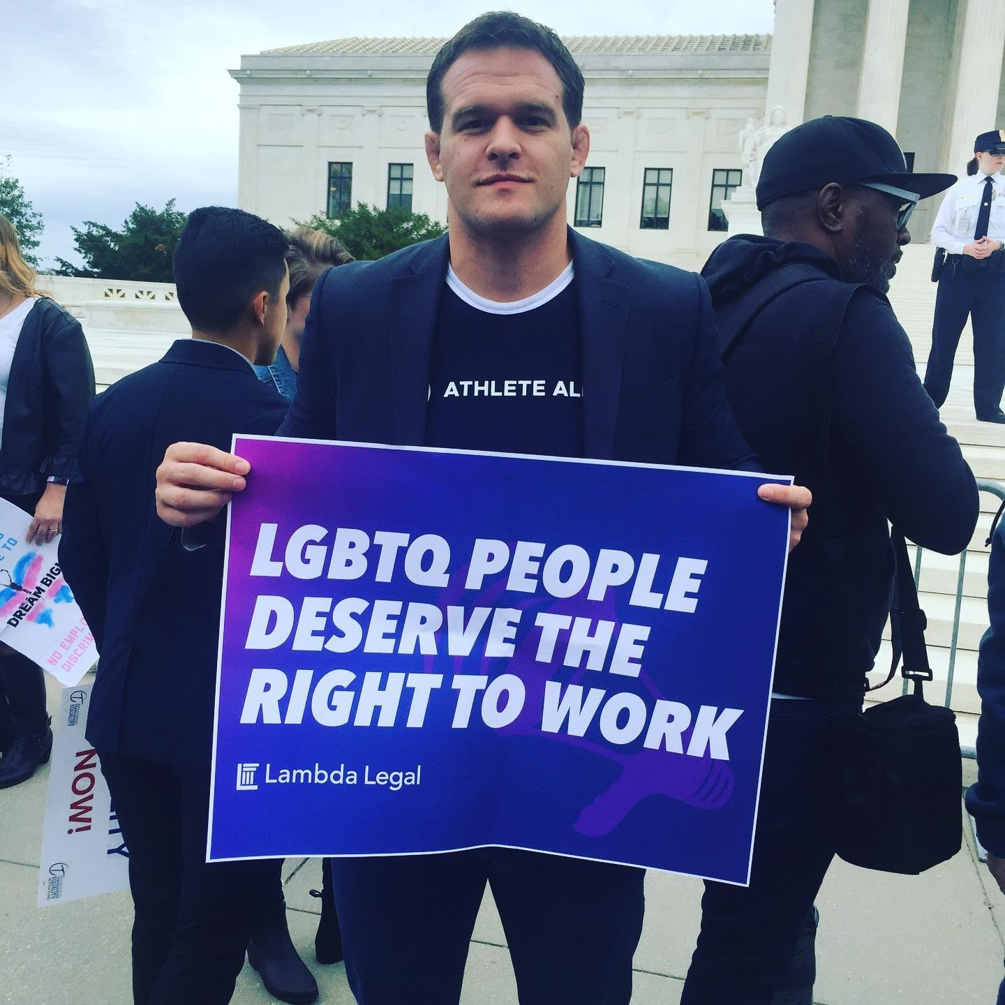 Man wearing dark suit holding up sign in support of LGBTQ people, Hudson Taylor, founder, Athlete Ally, LGBTQ, inclusion, diversity, protest