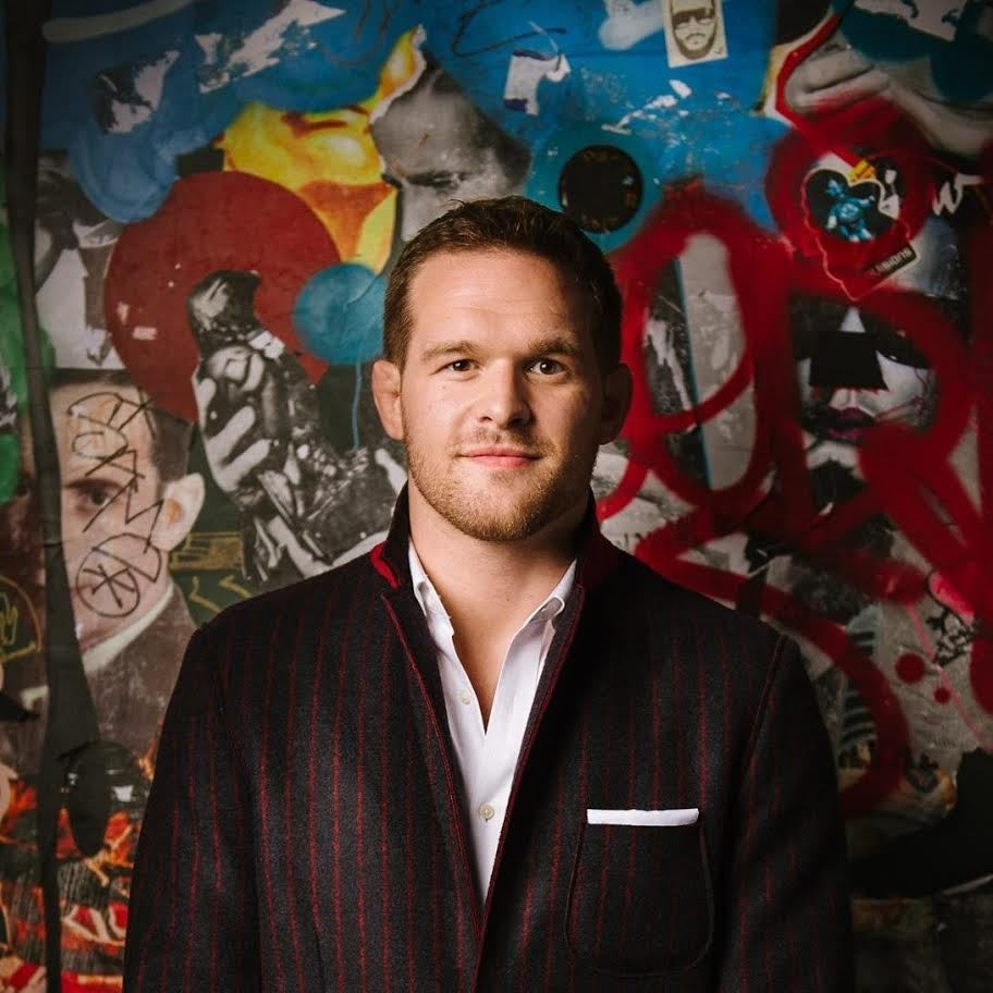 Headshot of Caucasian man wearing dark suit standing in front of graffiti wall, Hudson Taylor, founder, Athlete Ally, LGBTQ, charity