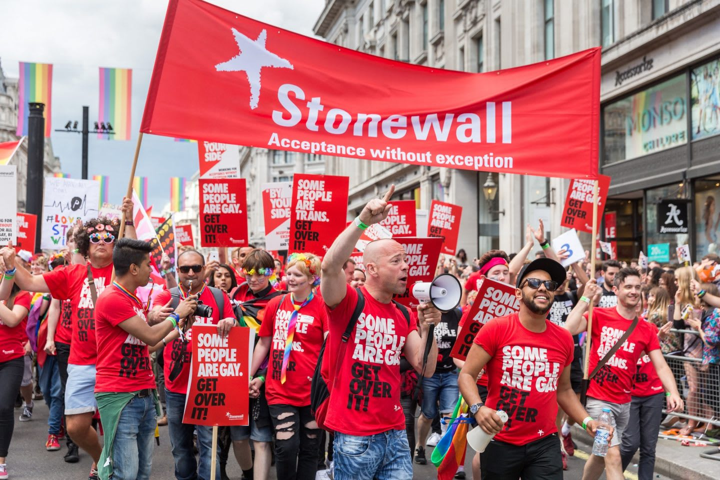 Men and women wearing red t-shirts during a march at London Pride Parade in 2016, Stonewall, LGBTQ, inclusion, diversity
