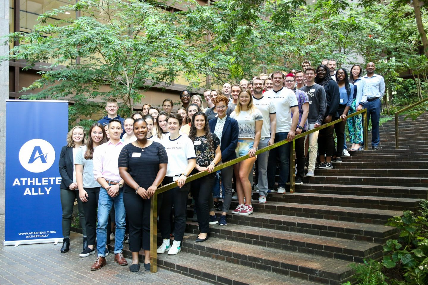 Men and women standing on steps in front of Athlete Ally sign, students, summit, conference, LGBTQ