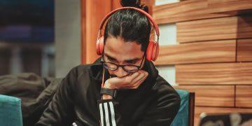 Man wearing glasses and orange headphones taking notes, podcast, learning, listening, adidas, development
