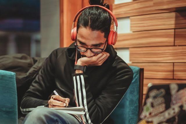 Man wearing glasses and orange headphones taking notes, podcast, learning, listening, adidas, development
