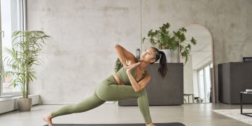 Woman in green yoga outfit in a yoga studio practicing yoga, healthy, lifestyle, stretching, exercise, fitness