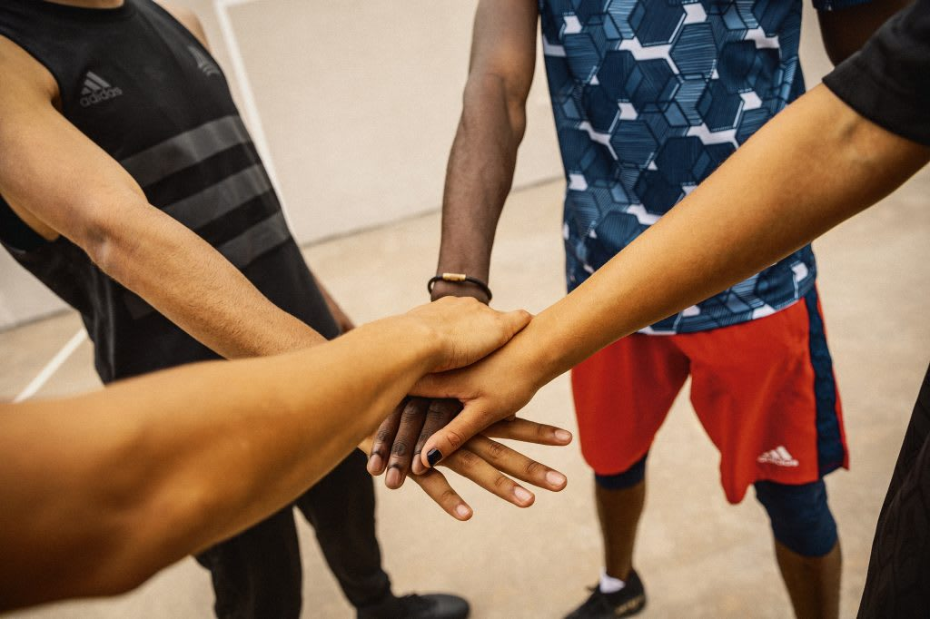 A group of people joining hands in a circle, teamwork, team, diversity, inclusion, adidas