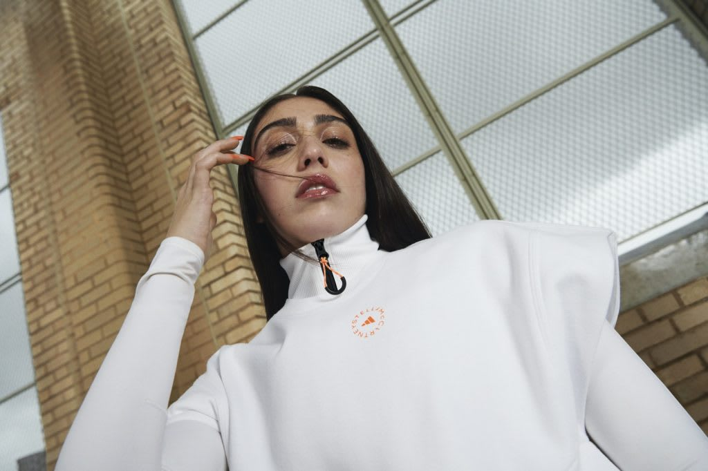 Woman with dark hair wearing white shirt and white jacket posing, Stella McCartney, style, sports, design