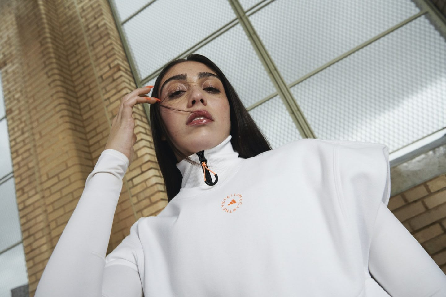 Woman with dark hair wearing white shirt and white jacket posing, Stella McCartney, style, sports, design
