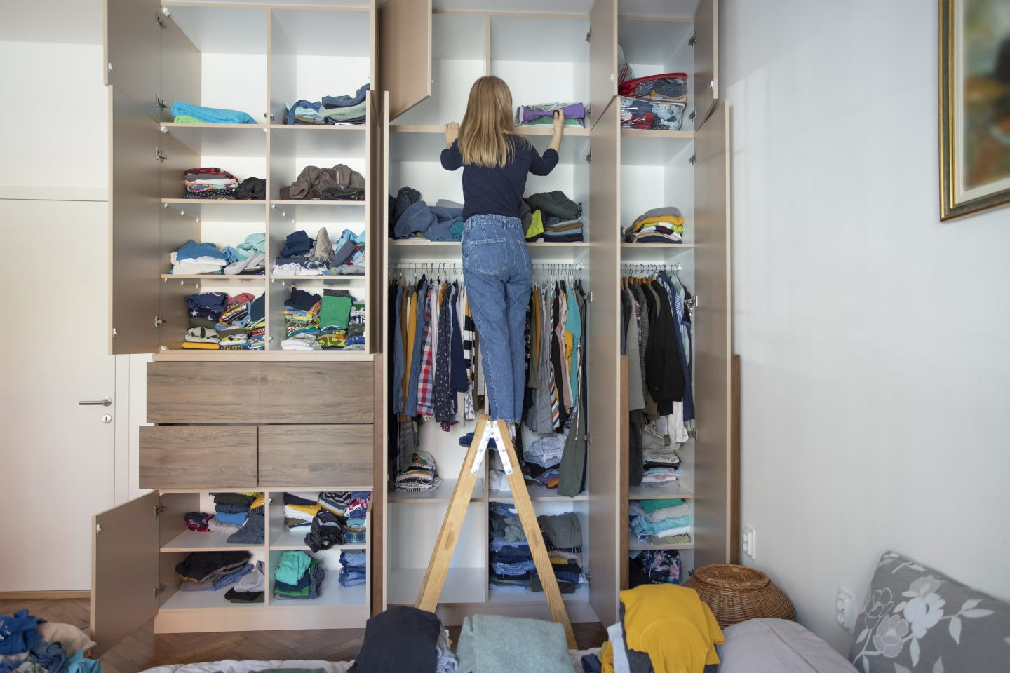 Young woman cleans up the mess in the closet, tidy, organization, clothes, wardrobe, closet, woman