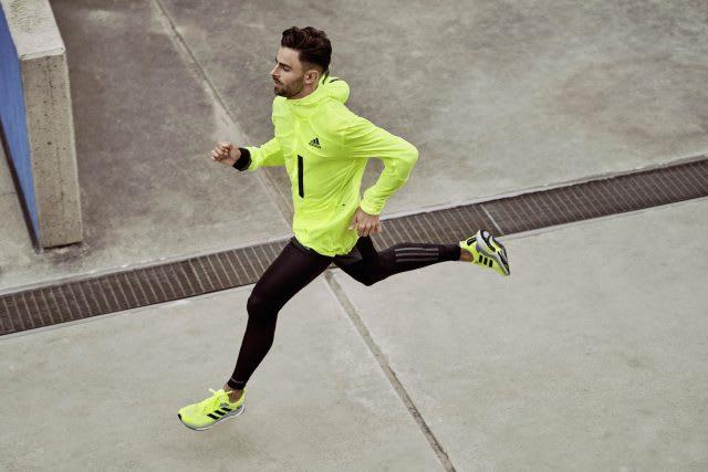 Man running in bright yellow running jacket and running shoes, adidas, Solarboost, athlete, running, run, runner. sports