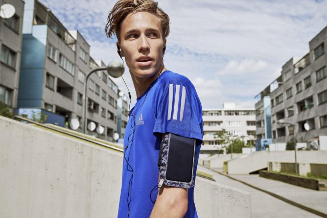 A runner wearing a blue adidas short and a mobile phone arm case. Business podcasts, adidas, GamePlan A