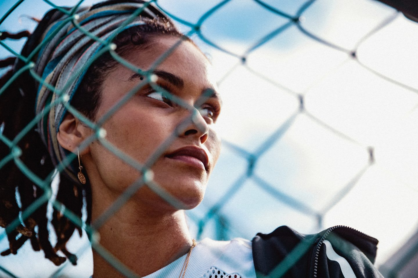 A woman looking out of the image behind a fence. mental health, podcast, health, lifestyle, adidas, GamePlan A