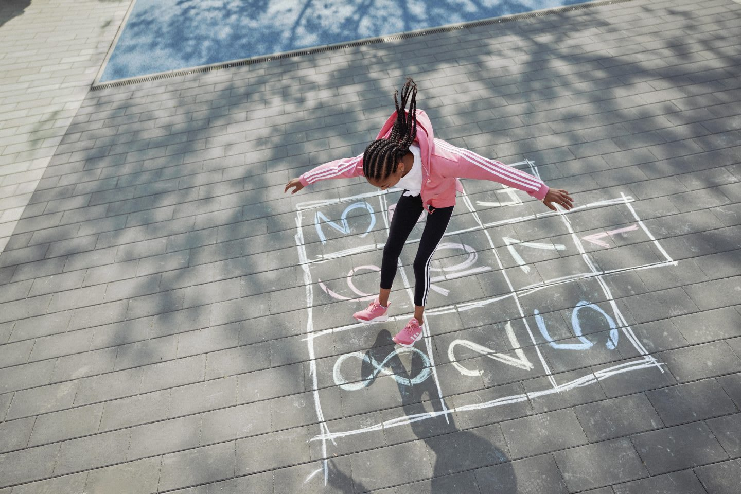 Girl playing in the playground with numbers drawn in chalk on the ground, adidas, sports, movement, apparel