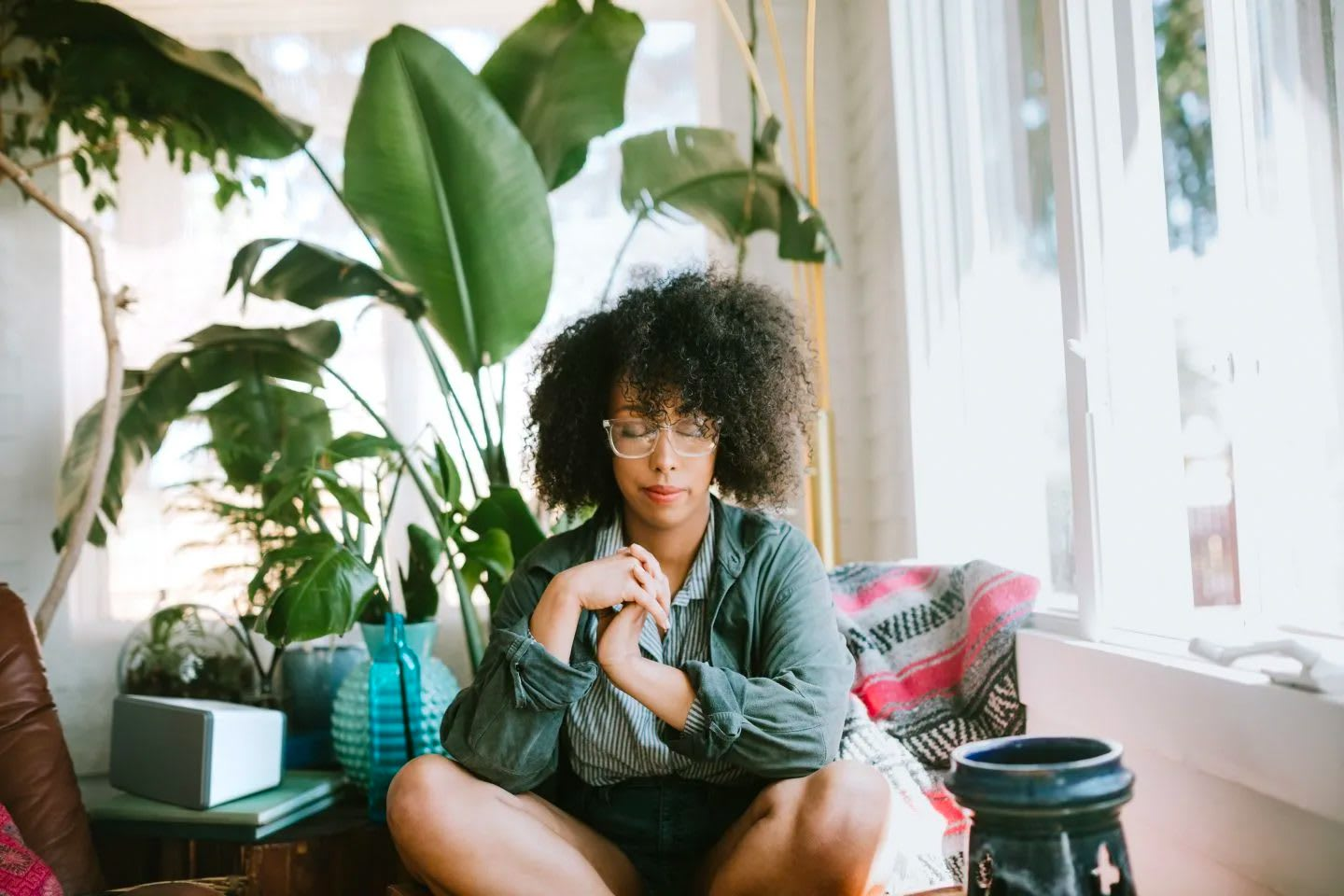 Woman with afro sitting cross-legged with eyes closed daydreaming, calm, peaceful, mindfulness