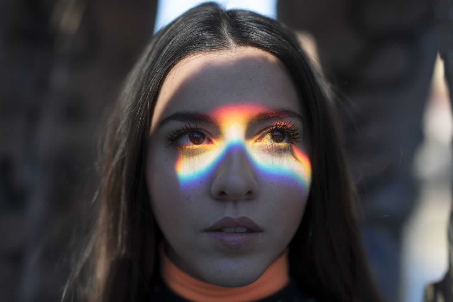 Close-Up Of Young Woman Looking Away with rainbow shadow on her face