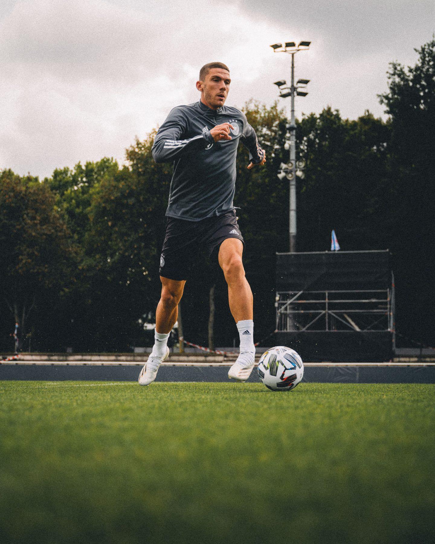 Caucasian man running and kicking a footballer on a grassy pitch, Robin Gosens, footballer, football, German, Germany, team, adidas, sports, exercise, DFB