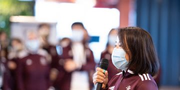 Women wearing medical mask and maroon jacket holding a microphone and giving speech in front of crowd, Hoa Ly, adidas, employees, Sourcing, women