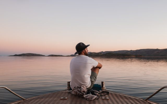 Man sitting on a boat on a lake at sunset staring out thoughtfully, alone, thoughts, reflections