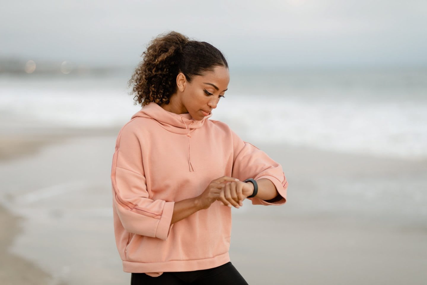 Woman wearing light pink hoodie checking her watch at the beach, outdoors, beach, seaside, woman, girl
