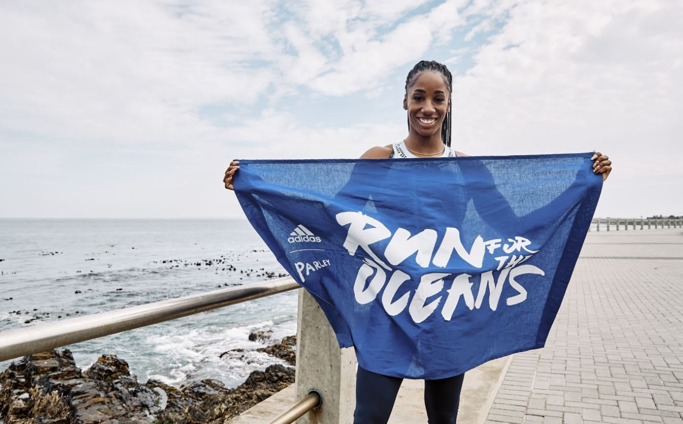 Woman holding Run For The Oceans flag in front of ocean, adidas, sustainability, plastic, waste, sports, purpose, GamePlan A