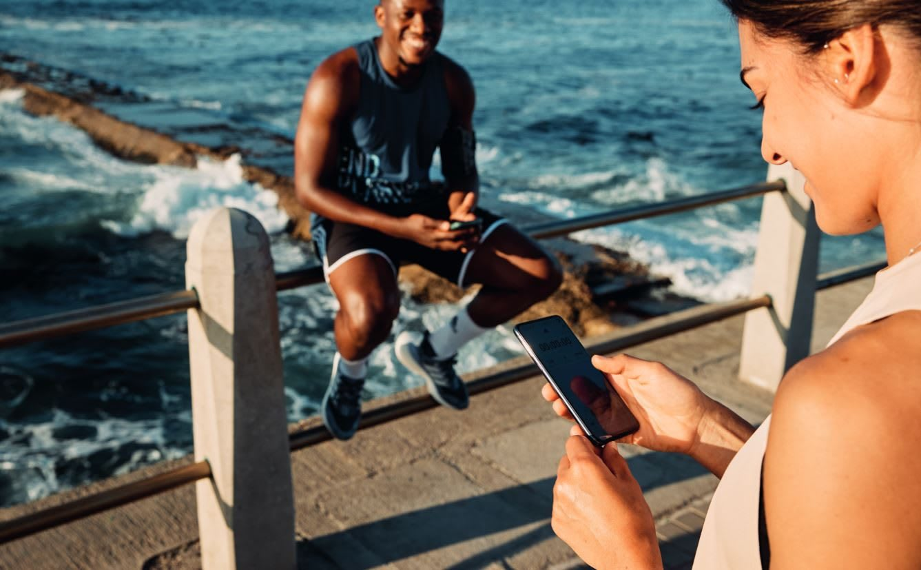 Woman looking at mobile phone by ocean, adidas, sports, fitness, running, Run For The Oceans, sustainability, plastic, waste, event, GamePlan A