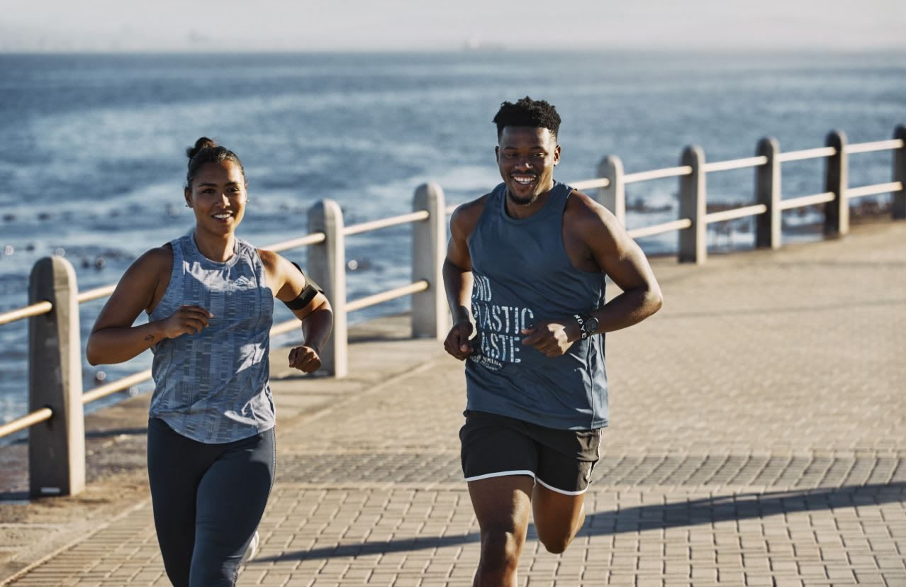Woman and man smiling and running along the ocean, adidas, running, sports, fitness, Run For The Oceans, sustainability, plastic, waste, GamePlan A
